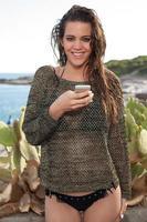 ragazza in spiaggia SMS su smartphone foto