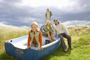 giovane famiglia seduta in barca foto