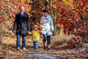 famiglia delle due generazioni che cammina nella vista frontale della foresta autunnale