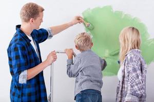 famiglia che vernicia la parete interna della casa foto