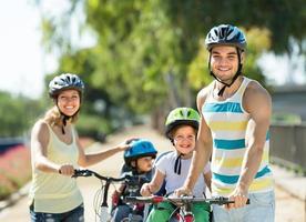 famiglia di quattro persone che viaggiano in bicicletta foto