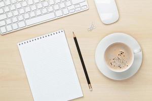 tavolo da ufficio con blocco note, computer e tazza di caffè foto