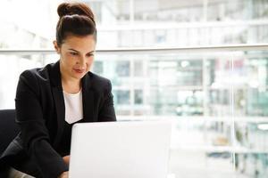 imprenditrice utilizzando il computer in interni moderni, mezzo busto foto