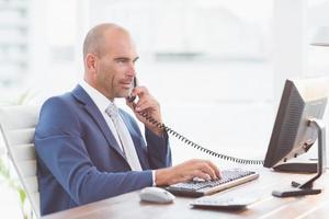 uomo d'affari al telefono e usando il suo computer foto