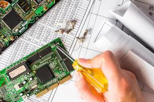 ripari il computer rotto, la mano che tiene un cacciavite foto