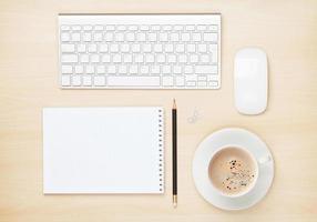tavolo da ufficio con blocco note, computer e tazza di caffè