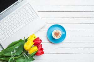 tazza di cappuccino a forma di cuore e computer