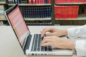 adolescente che utilizza computer portatile nella biblioteca foto
