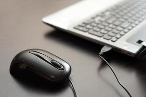 mouse e computer portatile cablato su un tavolo vicino foto