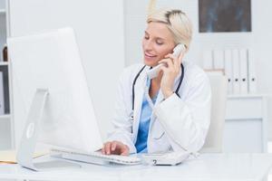 medico su chiamata mentre si utilizza il computer in clinica foto