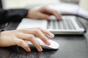 primo piano delle mani di una donna su un mouse e una tastiera foto