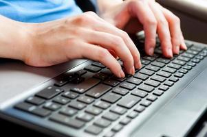 mani femminili toccando sulla tastiera del computer portatile d'argento da vicino foto