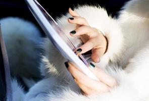 mani della donna che scrivono sul computer portatile bianco foto
