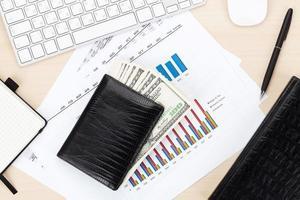 tavolo da ufficio con pc, forniture e denaro contante