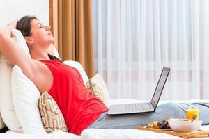 giovane donna addormentata con un computer in ginocchio foto