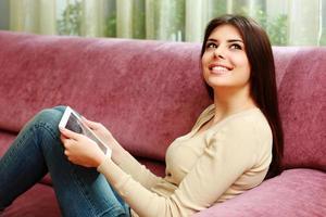 donna felice sdraiata sul divano con computer tablet foto