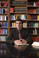 uomo pensieroso al banco della biblioteca foto