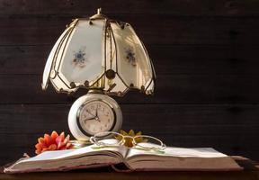 vecchia lampada e libri con occhiali da lettura foto