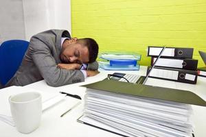 uomo d'affari indiano addormentato alla sua scrivania foto