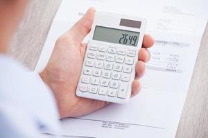 fattura calcolatrice delle mani dell'uomo d'affari allo scrittorio foto