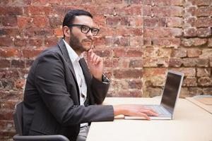uomo d'affari concentrato usando il portatile alla scrivania foto