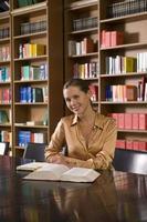 donna con libro alla scrivania in biblioteca foto