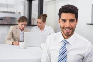 uomo d'affari sorridente con i colleghi alla scrivania foto