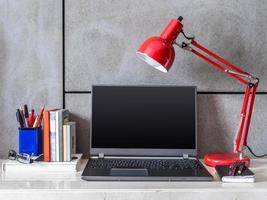 scrivania moderna con computer portatile e lampada foto