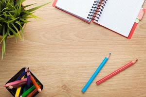 tavolo da ufficio con fiori, blocco note vuoto e matite colorate foto