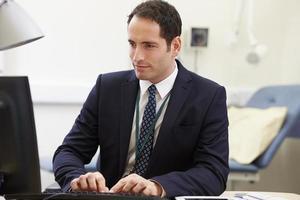 consulente maschio che lavora alla scrivania in ufficio foto