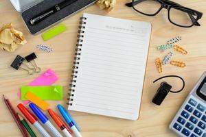 taccuino in bianco con articoli per ufficio sulla scrivania foto