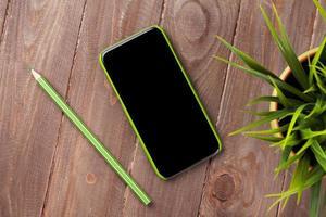 scrivania in legno con smartphone e pianta foto