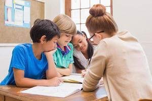 insegnante e alunni lavorano insieme alla scrivania foto