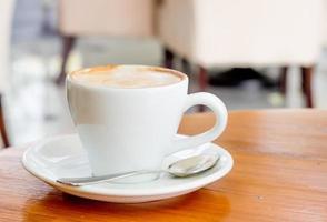 tazza di caffè latte sulla scrivania in legno foto