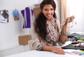 stilista femmina sorridente seduto alla scrivania
