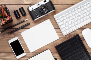 scrivania con forniture, macchina fotografica e scheda vuota foto