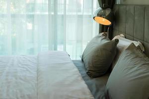 lampada da scrivania in metallo e cuscino grigio sul letto