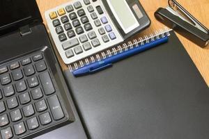 calcolatore e taccuino del fondo su una cucitrice meccanica dello scrittorio foto