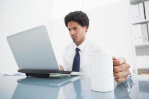 uomo d'affari facendo uso del computer portatile e tenendo tazza allo scrittorio foto