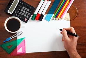 scrivania con foglio di carta e oggetti di cancelleria foto