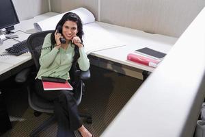 donna ispanica sul telefono alla scrivania cubicolo foto