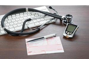 glucometro e ricetta sulla scrivania del medico foto