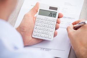 fattura calcolatrice dell'uomo d'affari allo scrittorio foto