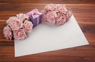 Saluto carta bianca con rose e regali foto
