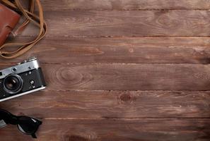 macchina fotografica e occhiali da sole sullo scrittorio di legno foto