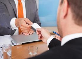 due uomini d'affari in possesso di carta sulla scrivania foto