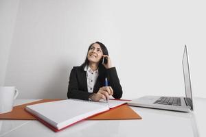 donna di affari che per mezzo del telefono cellulare alla scrivania foto