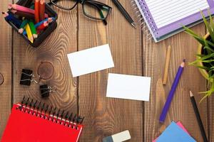 tavolo da ufficio con blocco note, matite colorate, forniture e busine foto
