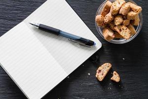 spuntino di lavoro - biscotti, blocco note, penna foto