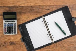 taccuino e penna con calcolatrice sulla scrivania foto